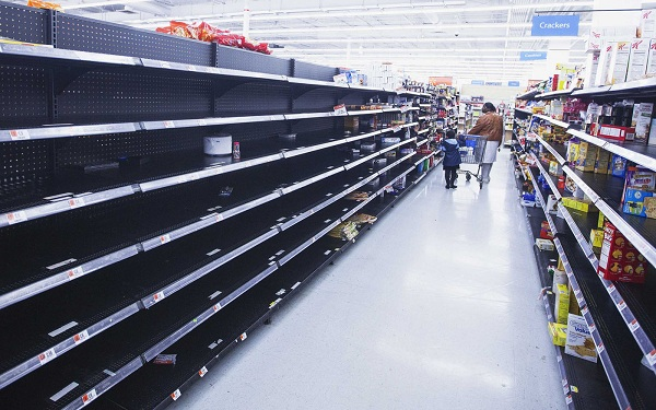 A woman and child walk through an aisle, emptied in preparation for Hurricane Sandy, in a Wal-Mart store in Riverhead